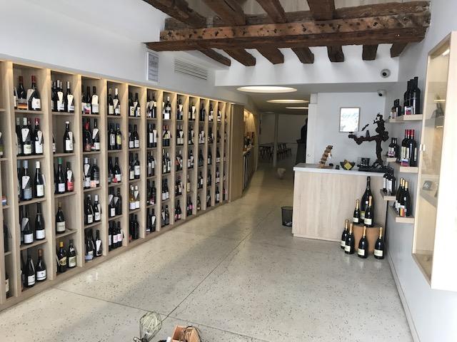 Salle avec des tables et des bouteilles de vin dans des étagères