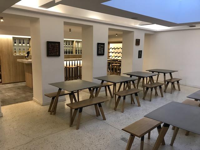 Salle avec des tables et des bouteilles de vin